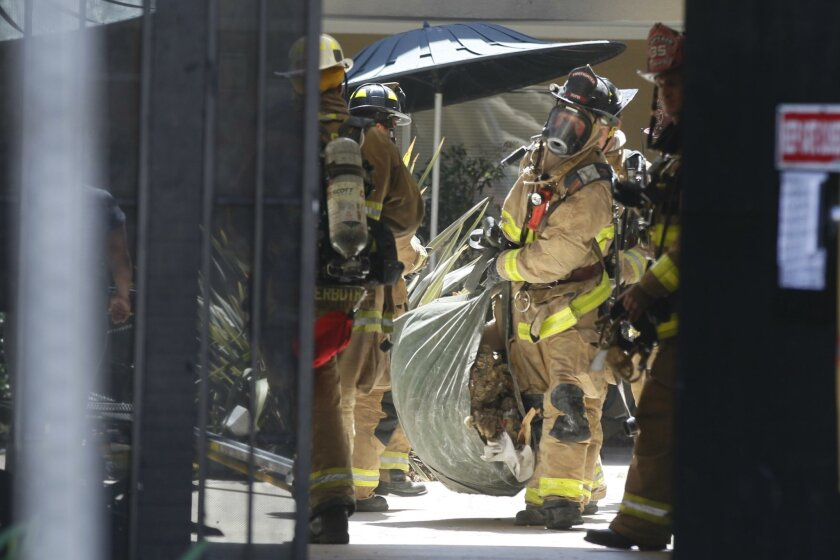 Firefighters hauled debris from a second story apartment  after they stopped a  fire in the wall from spreading to the attic of the Ocean Beach Complex.
