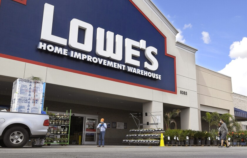 FILE - In this March 22, 2020 file photo, customers wearing masks walk into a Lowe's home improvement store in the Canoga Park section of Los Angeles. Lowe's announced Wednesday, Oct. 7, 2020 that it is handing out another round of bonuses to recognize its front-line employees in light of the COVID-19 pandemic. (AP Photo/Mark J. Terrill)