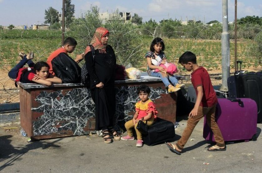 Palestinians wait at the Rafah border terminal in the southern Gaza Strip before crossing into neighboring Egypt on Saturday.