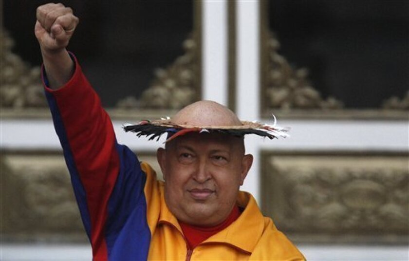 Venezuela's President Hugo Chavez raises his fist into the air after being presented with a 'healing hat' by an indigenous woman outside the Miraflores presidential palace in Caracas, Venezuela, Saturday Sept. 10, 2011. Chavez was visited by a group of Venezuela's indigenous community, who sang and