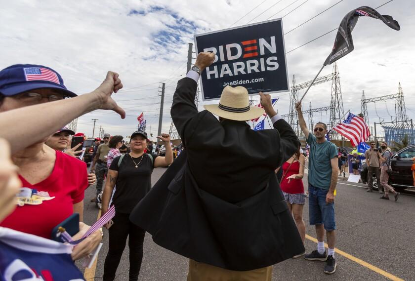 A supporter of Joe Biden walks through a crowd of Trump supporters in Phoenix on Nov. 6.