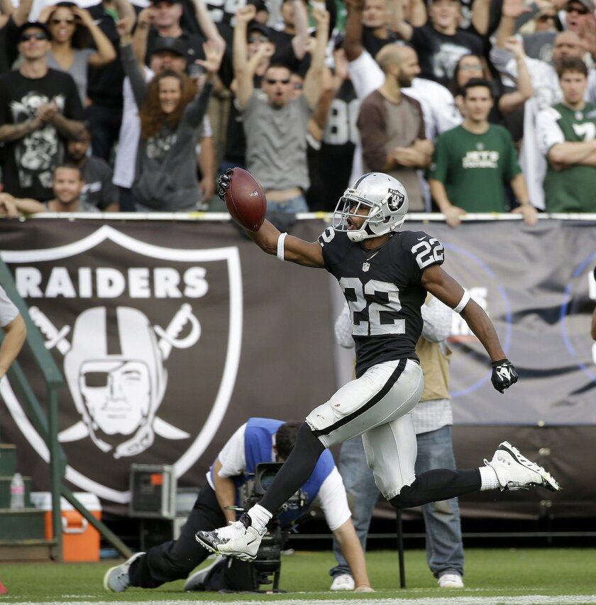 Oakland Raiders running back Taiwan Jones (22) runs toward the end zone to score on a touchdown reception during the second half of an NFL football game against the New York Jets in Oakland, Calif., Sunday, Nov. 1, 2015. (AP Photo/Marcio Jose Sanchez)