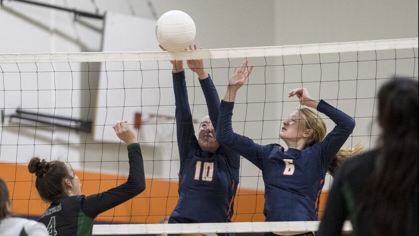Pacifica Christian's Allyson Sharrer and Casie Carlson block a hit by Orangewood Academy's Hannah Mo