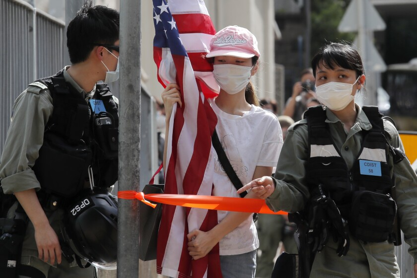 "A protester carrying an American flag as she is stopped by riot police during a protest outside the U.S. Consulate in Hong Kong, Saturday, July 4, 2020 to mark the American Independence Day or ""the Fourth of July."" China's government and pro-Beijing activists in Hong Kong are condemning what they call foreign meddling in the territory's affairs, as countries move to offer Hong Kongers refuge and impose sanctions on China over a new security law. (AP Photo/Kin Cheung)"