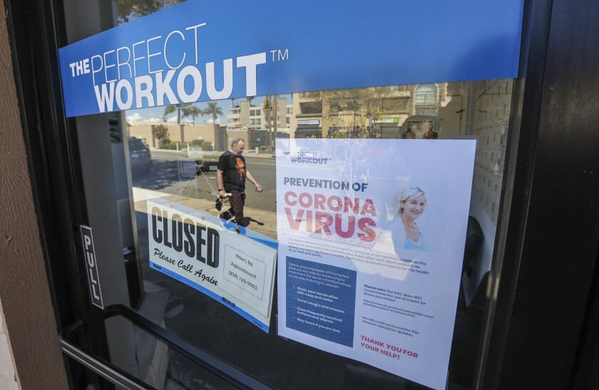 The Perfect Workout in La Jolla with closed and coronavirus-related signs on its door.