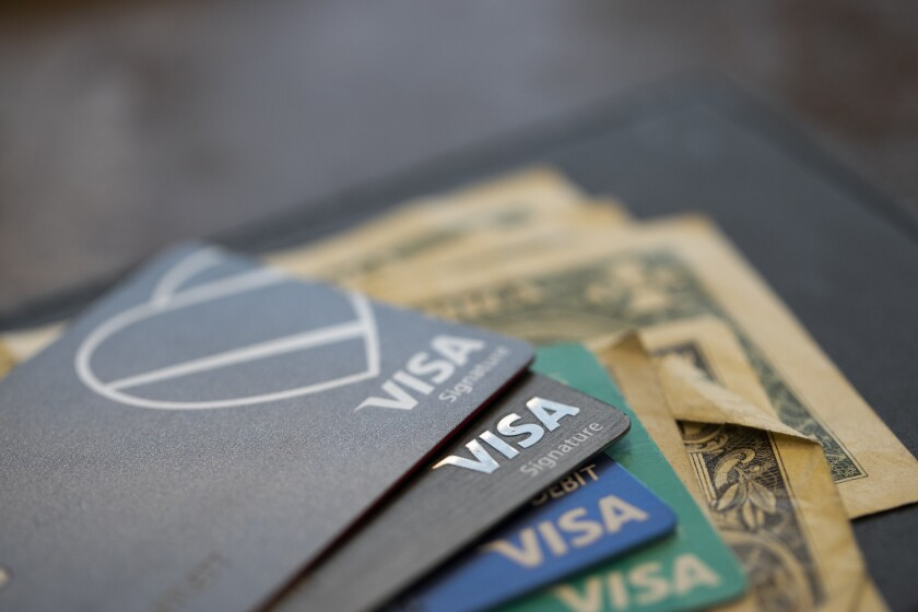 This Aug. 11, 2019, photo shows Visa credit cards and debit cards in New Orleans. If you're considering a new credit card, the bonus-friendly season from October through December is an ideal time. Your expenses on Black Friday, holiday travel and meals, end-of-the-year charitable donations and more may easily meet a large spending requirement for a juicy sign-up bonus. (AP Photo/Jenny Kane)