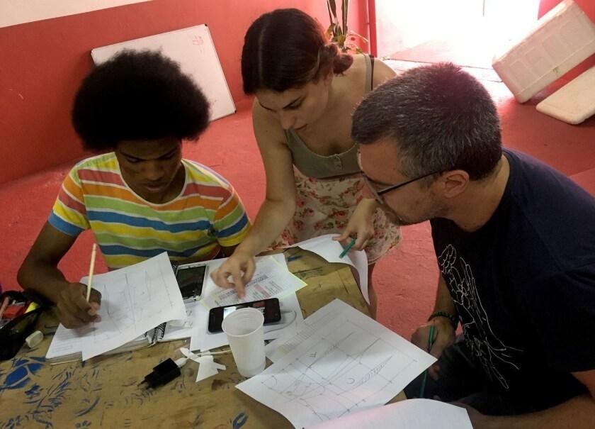 Nawira Scarano (centro) enseña a Reinaldo da Silva Freitas Jr. (izq.) y a otra estudiante cómo usar las medidas para hacer un patrón en su clase de costura, en el centro comunitario Casa 1, en San Pablo, Brasil (Jill Langlois / para Los Angeles Times).