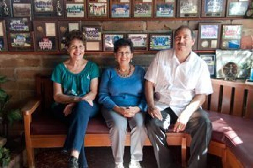 """Teresa Rincon, Catalina """"Liza"""" Salgado and Rincon's son, Ray, sit in Tony Jacal's entryway, which is decorated from wall to wall with photos of Little League teams the restaurant has sponsored. Photo/Claire Harlin"""
