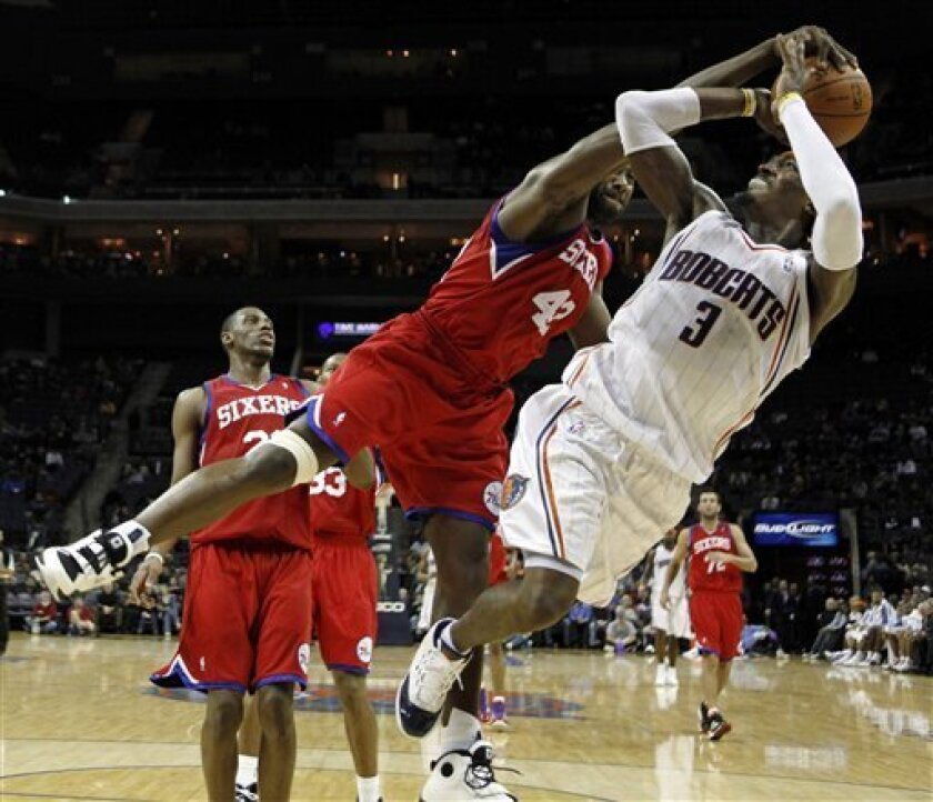 Charlotte Bobcats' Gerald Wallace (3) is fouled by Philadelphia 76ers' Elton Brand (42) as he shoots in the first half of an NBA basketball game in Charlotte, N.C., Saturday, Dec. 5, 2009. (AP Photo/Chuck Burton)