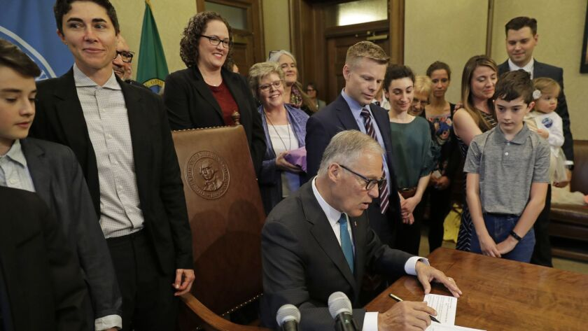 """Katrina Spade, second from left, the founder and chief executive of Recompose, a company that hopes to use composting as an alternative to burying or cremating human remains, looks on Tuesday as Washington Gov. Jay Inslee signs a bill into law allowing """"human composting."""""""