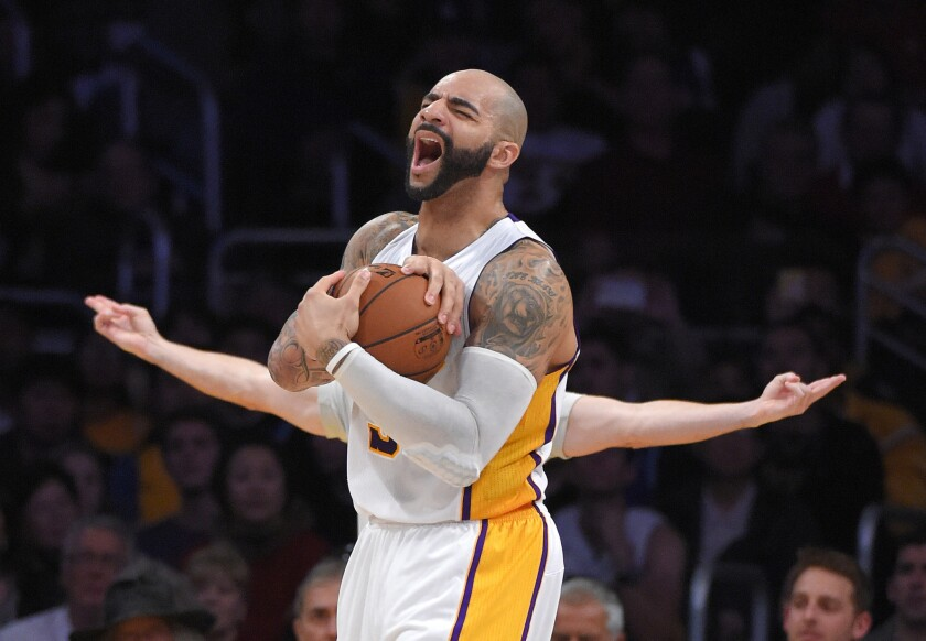 Lakers forward Carlos Boozer reacts after he's called for a foul by referee Eli Roe (background, arms extended) in the second half.