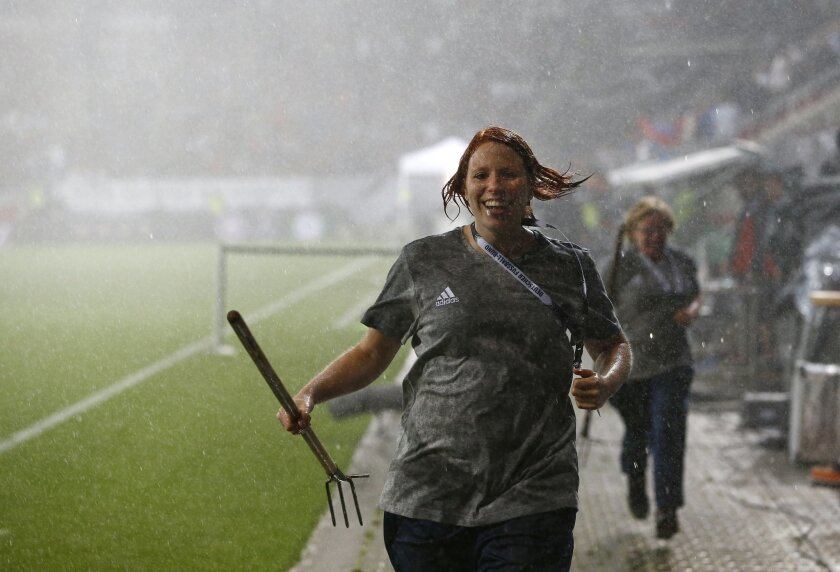 Green keepers run through the pouring rain during halftime of a friendly soccer match between Germany and Slovakia in Augsburg, Germany,  Sunday, May 29, 2016. (AP Photo/Matthias Schrader)