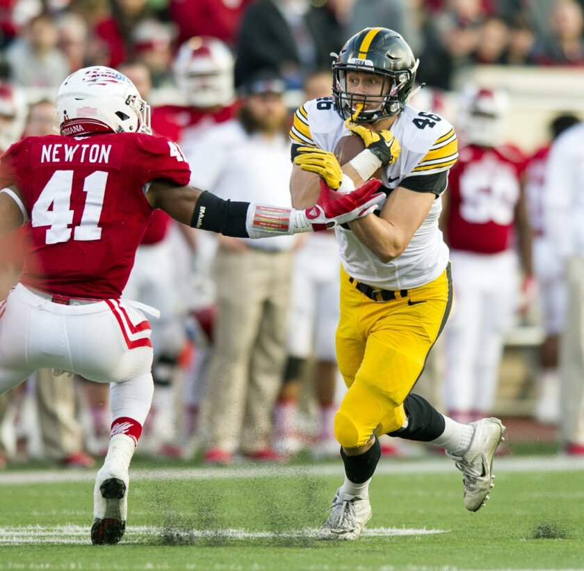 Iowa tight end George Kittle (46) holds onto the ball as he tries to elude the tackling effort to Indiana linebacker Clyde Newton (41) during the first half of an NCAA college football game in Bloomington, Ind., Saturday, Nov. 7, 2015. (AP Photo/Doug McSchooler)