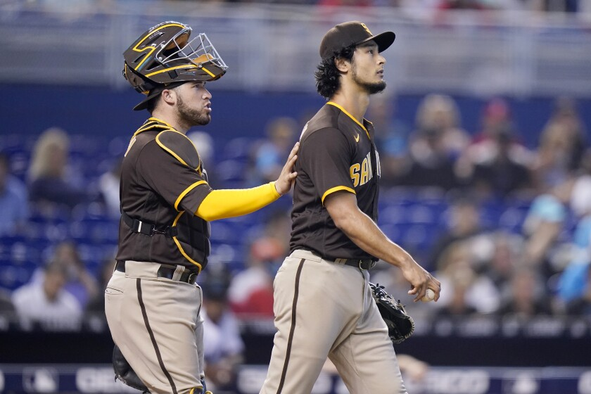 Padres catcher Victor Caratini talks with starting pitcher Yu Darvish during Sunday's game at Miami.
