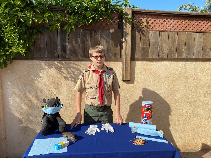 Killian Treppa, a Boy Scout in Point Loma-based Troop 500, shows the supplies he's used to make masks for his Eagle project.