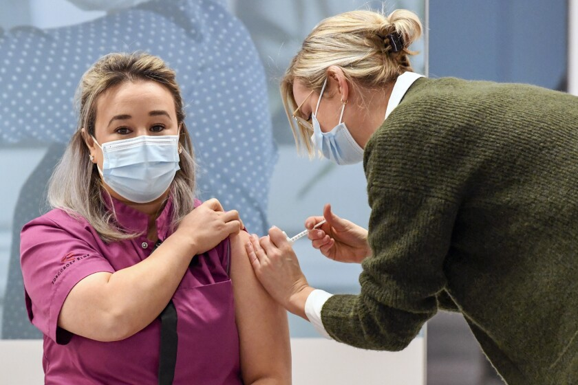 Healthcare worker Sanna Elkadiri, left, was the first Dutch recipient of a shot of the Pfizer-BioNTech coronavirus vaccine at a mass vaccination center in Veghel, Netherlands, Wednesday Jan. 6, 2021. Nearly two weeks after most other European Union nations, the Netherlands on Wednesday began its COVID-19 vaccination program, with care home staff and frontline workers in hospitals first in line for the shot. (Piroschka van de Wouw/Pool via AP)