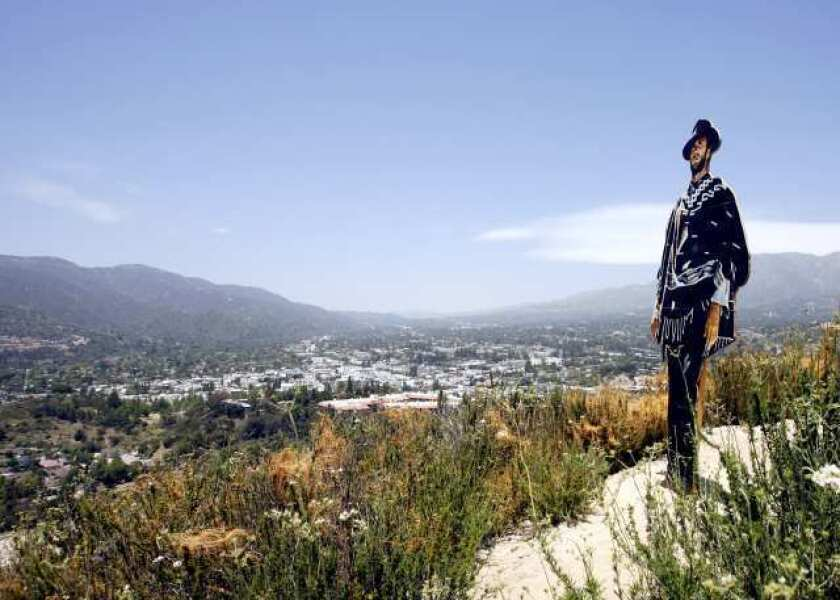 Ernie Hess of Montrose looks at a cut out of Clint Eastwood placed on a ridge at the top of the Verdugo Hills overlooking the Glendale (2) Freeway, on Wednesday, May 23, 2012.