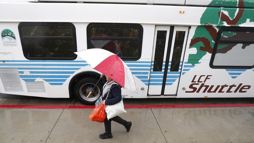 La Canada High School students pull out umbrellas and hustle as heavy rain starts to fall just as th