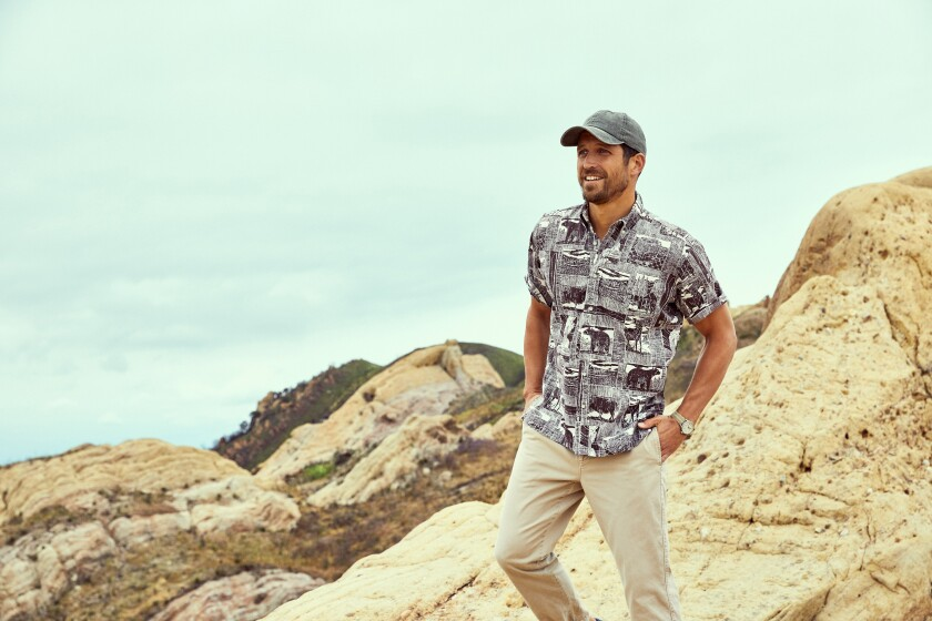 A man standing on rocks models Reyn Spooner's Yellowstone shirt.