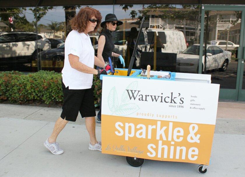 La Jolla Village Merchants Association Board member Nancy Warwick (in black) and Sparkle & Shine employee Nancy Deering pick up litter along Fay Avenue on April 1, 2015. the first day of the association's new trash collection program.