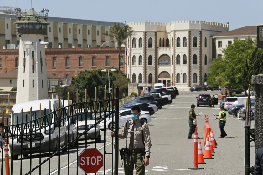 FILE - In this July 9, 2020, file photo, a correctional officer closes the main gate at San Quentin State Prison in San Quentin, Calif. A federal judge on Monday, Sept. 27, 2021, ordered that all employees entering California prisons be vaccinated or have a religious or medical exemption to vaccination as he tries to head off another outbreak like the one that killed 28 inmates and a correctional officer at San Quentin State Prison last summer. (AP Photo/Eric Risberg, File)