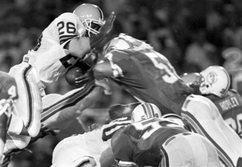 FILE - In this Aug. 16, 1986, file photo, Miami Dolphins linebacker Jay Brophy (53) leaps over the line of scrimmage unable to stop Cleveland Browns running back Greg Allen (26) from scoring the game-winning touchdown in the fourth quarter of a preseason NFL football game in Miami. Brophy is now 53
