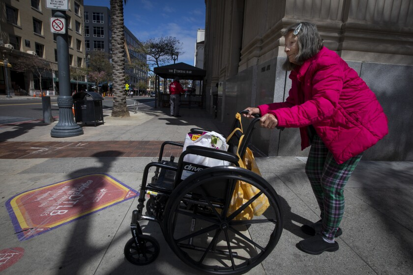 Rhonda Summerlin, 70, of Carson pushes her wheelchair down a Long Beach sidewalk on Sunday to pick up medicine and food.
