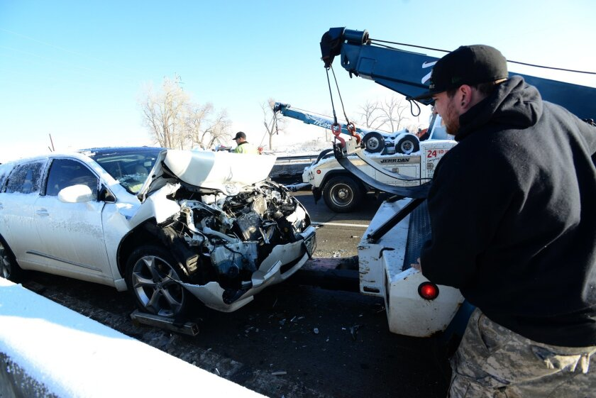 A tow truck driver works to clear the scene of a multi-vehicle pileup on U.S. Highway 36, Friday, April 3, 2015 near Boulder, Colo. Numerous crashes and spin outs on icy and snowy highways have closed portions of several interstates and highways in the Denver and Colorado Springs area as well as the mountains. (AP Photo/The Daily Camera, Paul Aiken) NO SALES