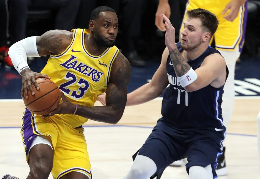 The Lakers' LeBron James dribbles the ball against the Dallas Mavericks' Luka Doncic.