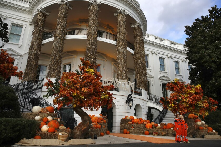 Two girls pose for a photograph with the decorated South Portico of the White House, Sunday, Oct. 28, 2018, in Washington, ahead of a Halloween event with President Donald Trump and first lady Melania Trump.