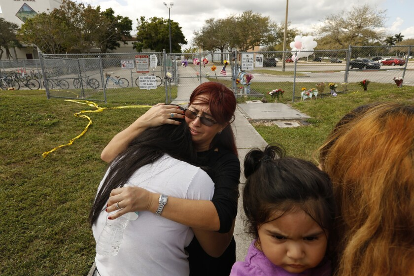 Abigail Avioa, a senior at Marjorie Stoneman Douglas High School, her back to camera, is prayed over in front of the school on Sunday, Feb. 18, 2018.