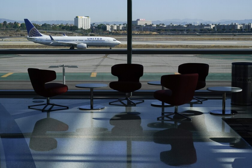 An airplane taxis past a gate at LAX