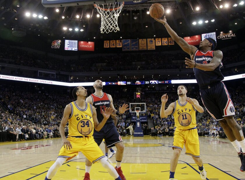 Washington Wizards' Bradley Beal, right, drives to the basket past Golden State Warriors' Klay Thompson (11), teammate Marcin Gortat (13) and Warriors' Shaun Livingston (34) during the first half of an NBA basketball game Tuesday, March 29, 2016, in Oakland, Calif. (AP Photo/Marcio Jose Sanchez)