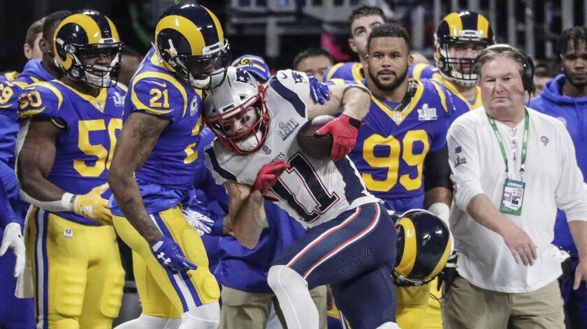 ATLANTA, GEORGIA, FEBRUARY 3, 2019 - Patriots receiver Julian Edelman leans into Rams defensive back