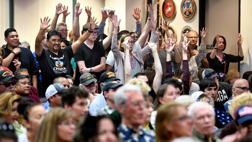 """Supporters of the """"sanctuary state"""" law raise their hands at Santa Clarita City Hall before a vote Tuesday."""