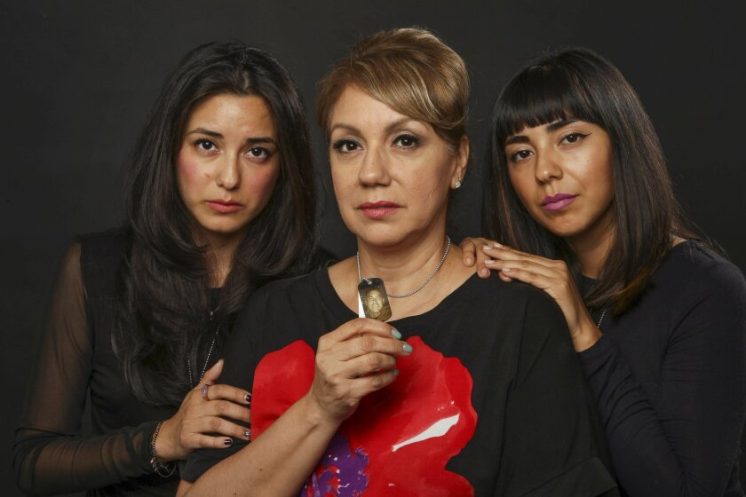Diana Cruz holds a dog tag with a dog tag picture of her son Air Force military policeman Mike Cruz, who died by suicide, with her daughters Morgan Cruz, left, and Marrisa Cruz.