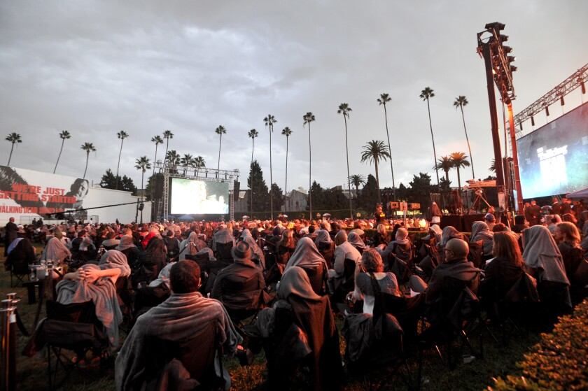 """Fans of """"The Walking Dead"""" brave the rain to watch the season premiere at Hollywood Forever Cemetery as part of a """"Talking Dead Live"""" event."""