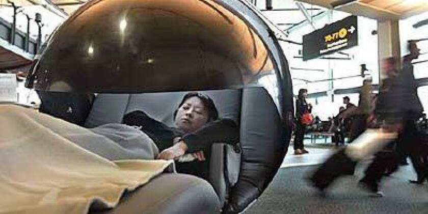 An airline passenger in the international departures lounge of Vancouver International Airport tries a sleeping pod offered by NapCentre
