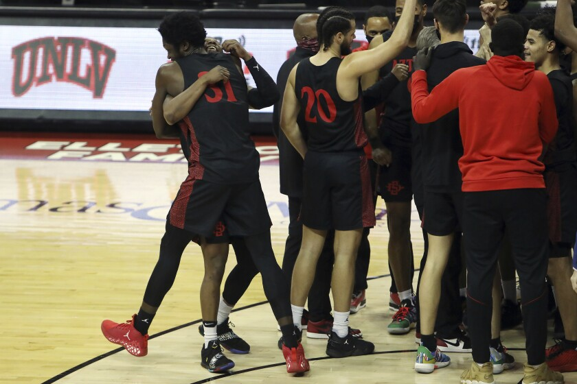 San Diego State players including Nathan Mensah (31) celebrate winning Mountain West title Wednesday at UNLV.