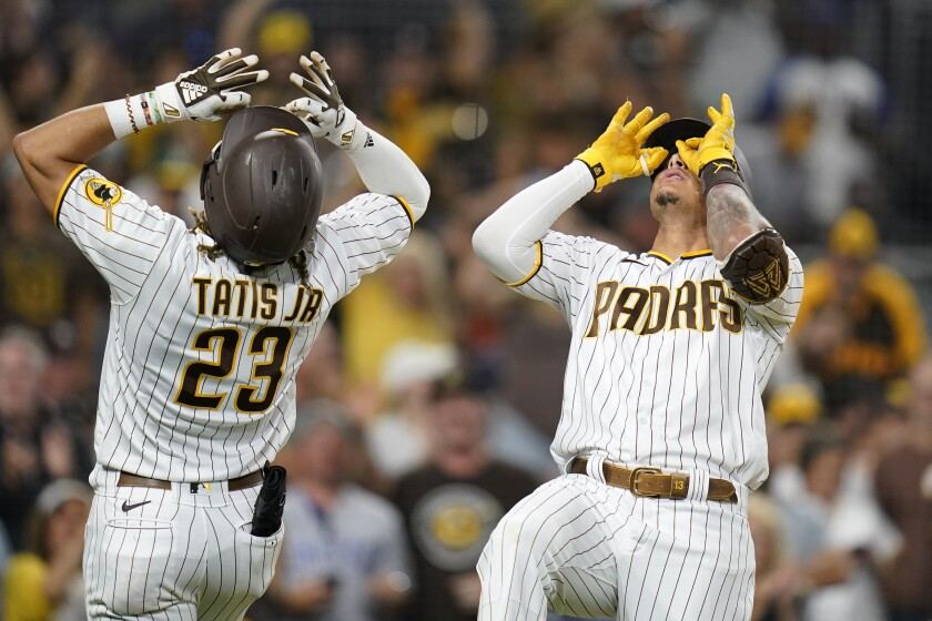 San Diego Padres' Manny Machado, right, reacts with teammate Fernando Tatis Jr. (23) after hitting a two-run home run during the seventh inning of a baseball game against the Houston Astros, Saturday, Sept. 4, 2021, in San Diego. (AP Photo/Gregory Bull)
