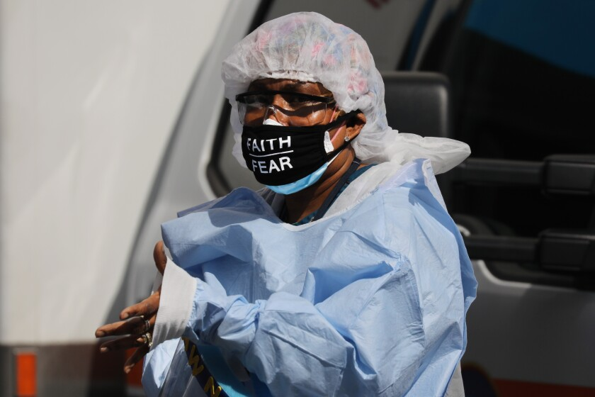 A medical worker with 'faith over fear' on her mask pauses outside a coronavirus intake area at Maimonides Medical Center in Brooklyn on Thursday.