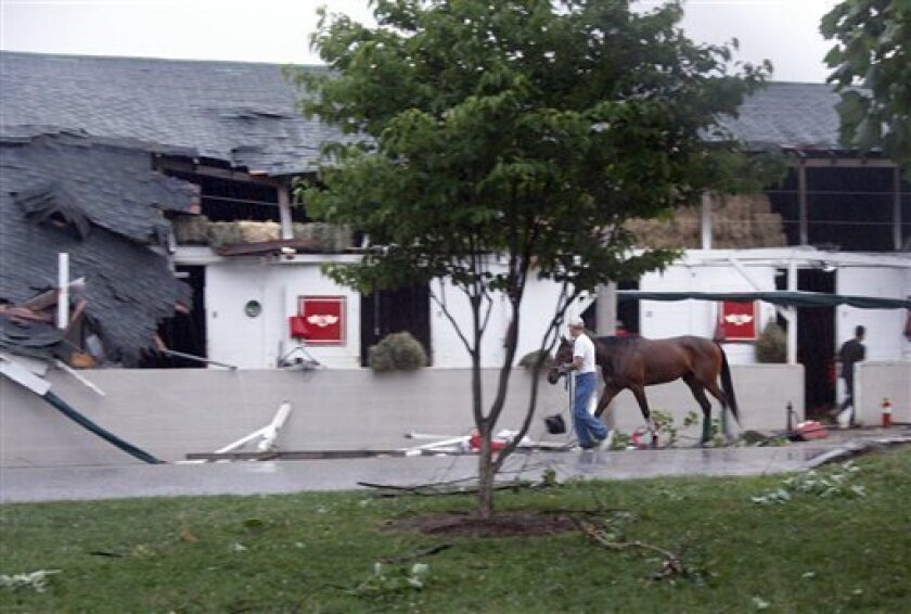 A horse is walked out of barn 40 which was damaged at Churchill Downs after storms passed through the area in Louisville, Ky., Wednesday, June 22, 2011. (AP Photo/The Courier-Journal, Pam Spaulding) NO SALES, NO ARCHIVE, MAGS OUT