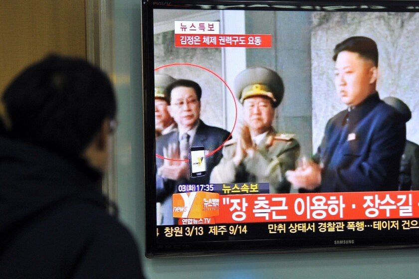 A television at a train station in Seoul shows a news program reporting the apparent ouster of Jang Song Taek (circled), the uncle of North Korean leader Kim Jong Un (right).
