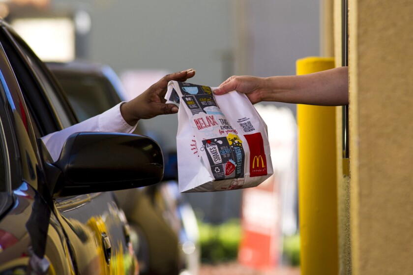 A customer receives an order at the drive-through of a McDonald's restaurant in San Pablo, Calif., on Jan. 22.