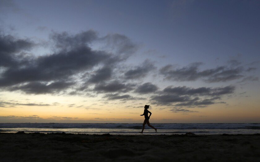 A jogger runs as the sunsets on a breezy afternoon at La Jolla Shores.