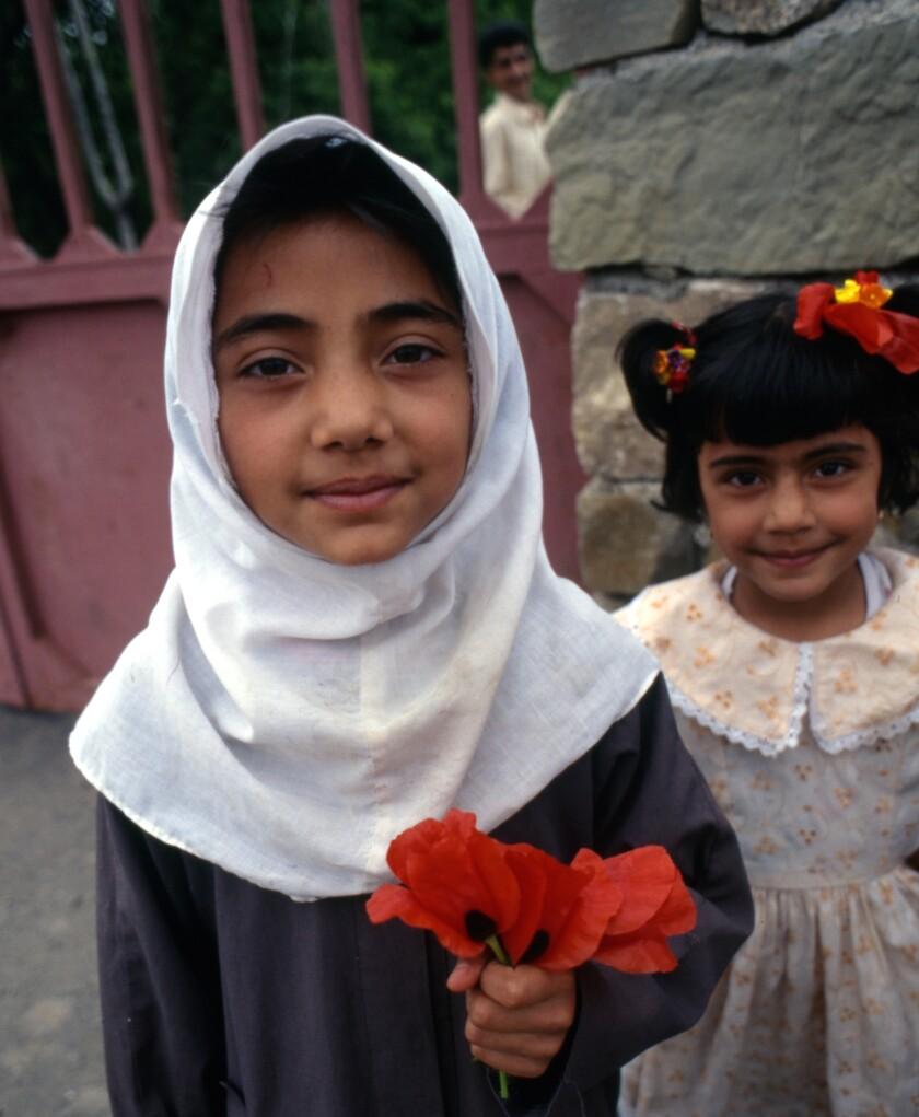 Schoolgirls greeted us south of Mashhad, bearing poppies. Iran, 1998.
