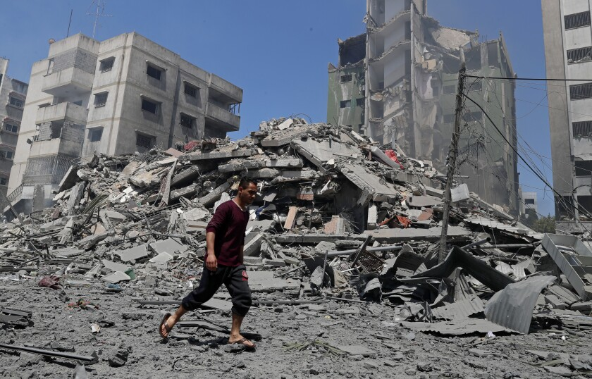 A huge pile of rubble and damaged high-rises serve as the backdrop to a man walking by