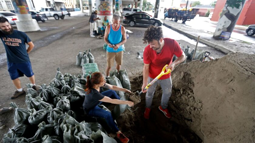Leah Perry, center, and her husband, Scott, fill sandbags in New Orleans.