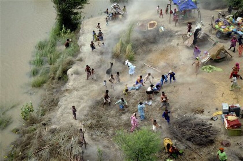 Pakistani villagers chase to relief supplies dropped from an army helicopter in a heavy flood-hit area of Mithan Kot, in central Pakistan, Monday, Aug. 9, 2010. The government has struggled to cope with the scale of the disaster, which has killed at least 1,500 people, prompting the international