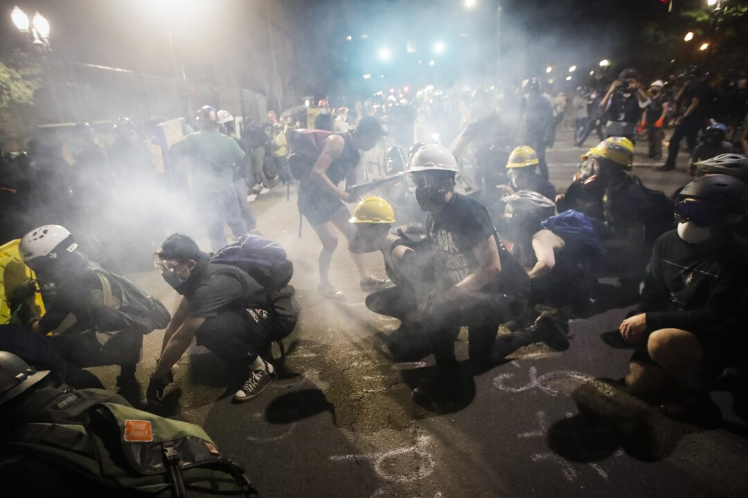 Demonstrators sit and kneel as tear gas fills the air during a Black Lives Matter protest in Portland, Ore.